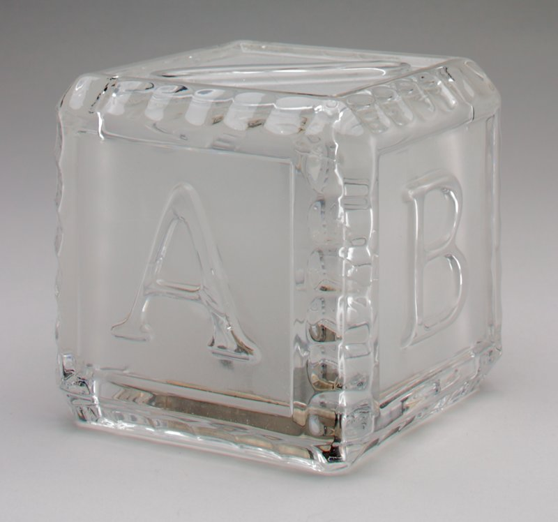 clear glass toy building block with letters A-D on 4 sides; coin slot on top and silver colored metal cover over bottom
