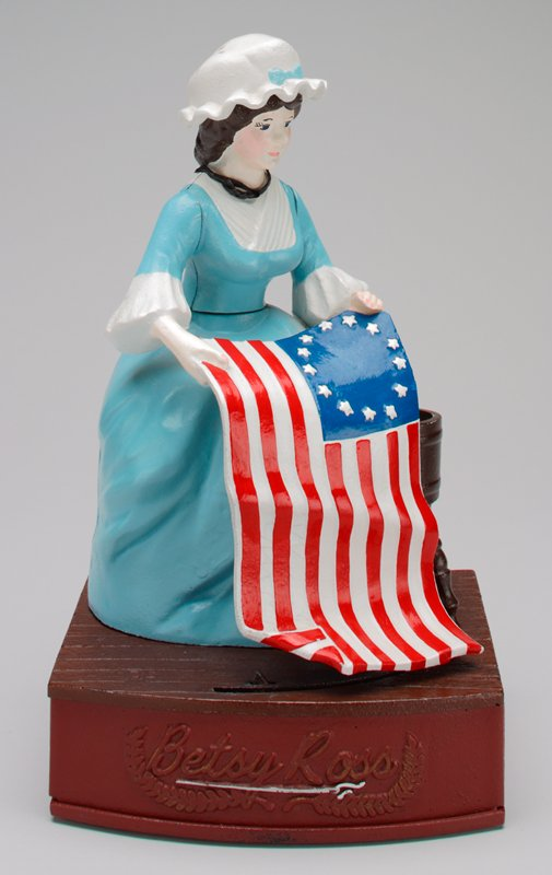metal bank with seated Betsy Ross in a blue dress holding a 13 star American flag; lever on back; American flag moves back and forth