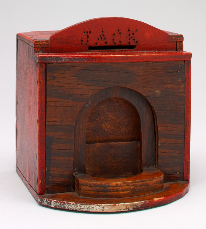 wood block shape painted red on the outside; archway (door?) front side; coin slot top front