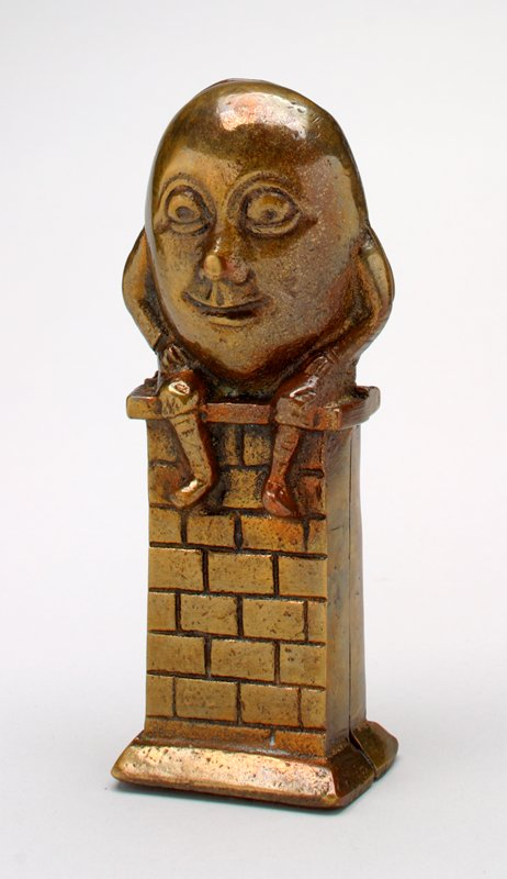 brass egg with face, arms and legs, Humpty Dumpty smiling and sitting on a brick wall; made in 2 parts- front and back