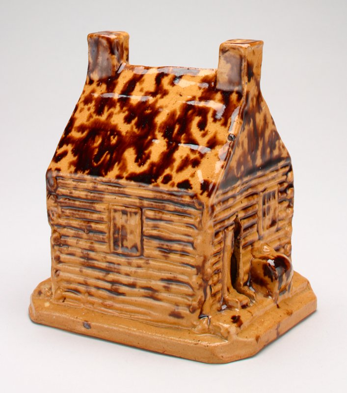 tan and brown ceramic log cabin with shiny glaze; 2 chimneys on roof; window door and wood pile at front and back, window on each side