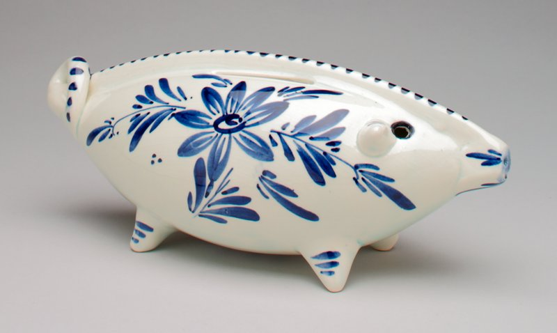 stylized Delft pig with long body and curly tail; flower designs on each side; stripes on each leg; coin slot on back