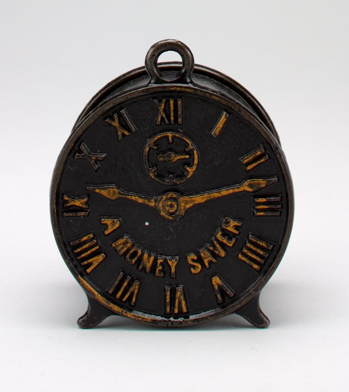 round black clock with Roman numerals in gold on face; gold hands and gold secondary dial; coin slot in back