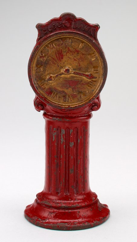 """red metal pedestal clock with gold face; Roman numerals on face; clock hands point to 8:17; at the top of the face are the words """"Clock Bank"""""""