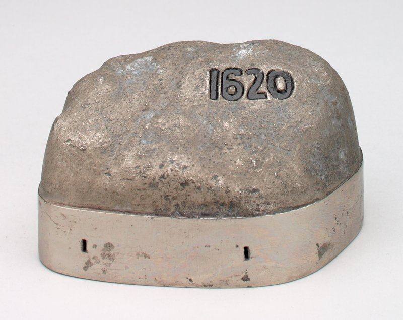 "metal facsimile of Plymouth Rock with silver metallic base; ""1620"" in black on the top front; coin slot on back of base with ""Plymouth Rock The Cornerstone Of A Nation"" above slot; ""On This Rock I Will Build My Fortune"" below the slot"
