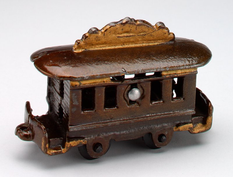 train car in 5 pieces: 2 sides, 2 wheel sets and a screw; car is dark metal trimmed with gold pigment; there are 4 windows in each side