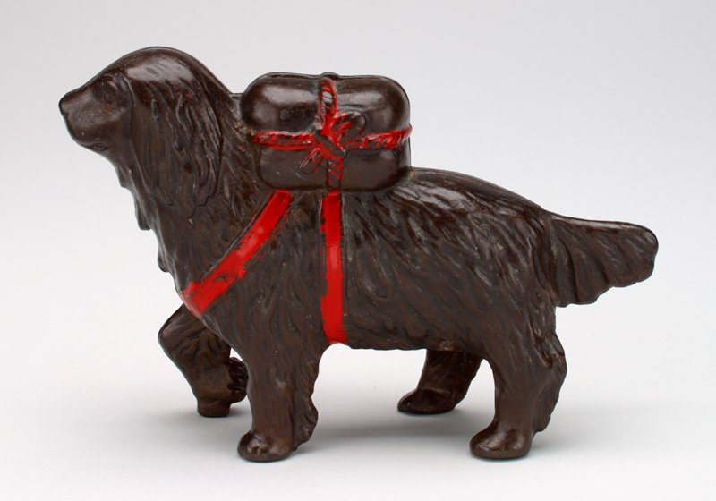 brown long-haired dog; package held on back by 2 red straps; package tied with red rope; coin slot in package