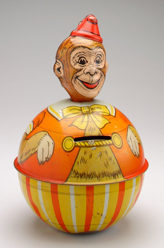monkey dressed in clown costume- orange jacket, orange, yellow and white stripes on pants; red hat; coin slot center front