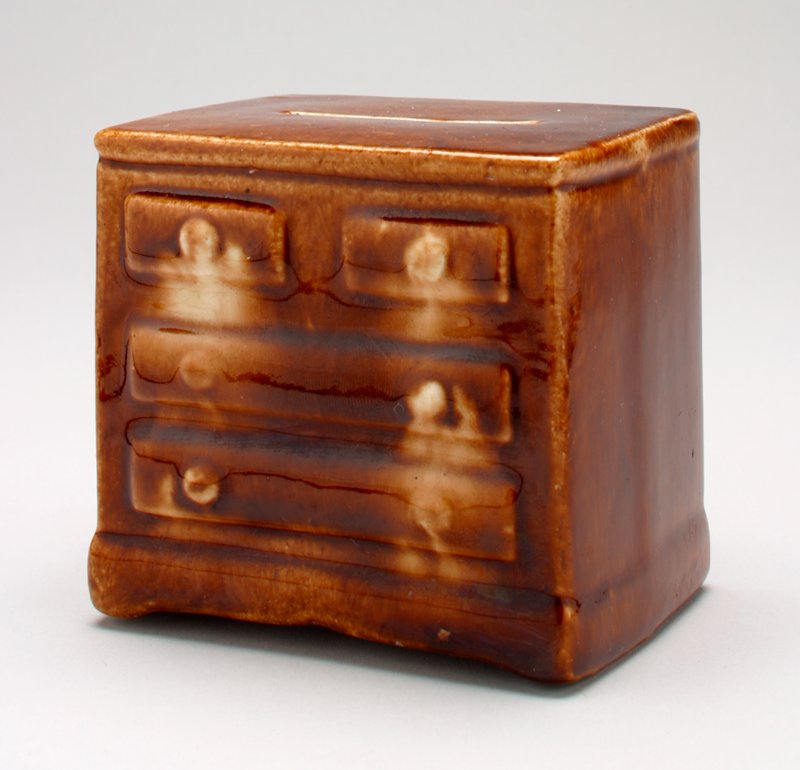 brown ceramic chest with 2 narrow drawers on top and 2 wide drawers on the bottom; shiny glaze; coin slot on top