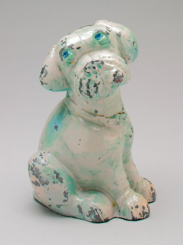 white metal seated dog looking up with floppy ears wearing a collar; he has blue eyes and green primer