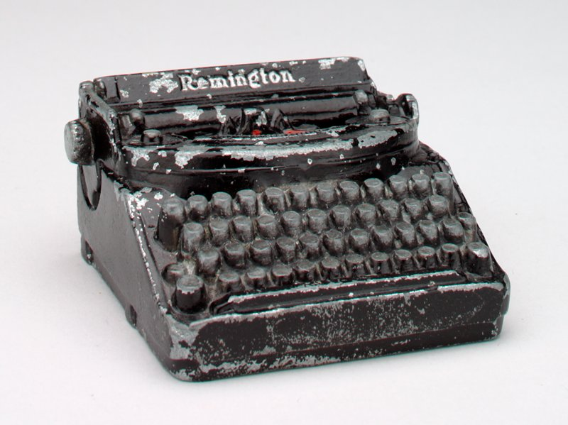 "black metal typewriter with red and black ribbon: ""Remington"" printed on top across the back; on back in silver: ""Electrical Products Building/ Remington Rand Hall/ New York/ World's Fair/ 1939"""