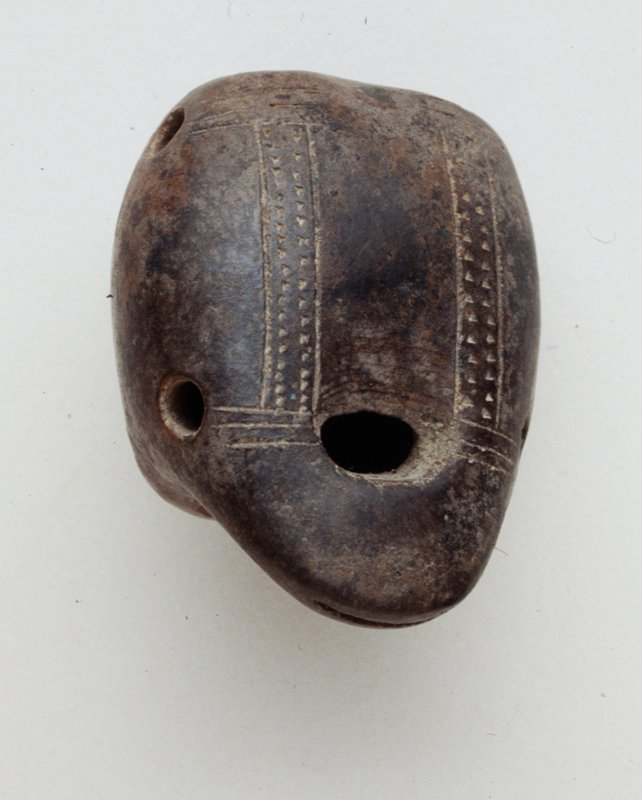 Four Note Whistle in the form of a stylized frog; two bottom suspension holes; incised linear designs on back burnished red slip, reduction fired