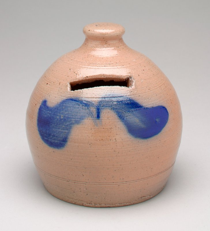 taupe-colored vessel with flat top knob and 2 blue swirls below coin slot in side; glazed ceramic