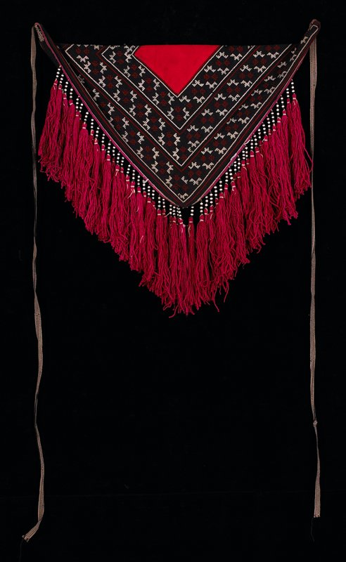 triangular, with stiff outer frame; pink tassels with black and white beads at top; triangular piece of blue fabric with red applique at bottom and white, maroon and blue cross-stitch