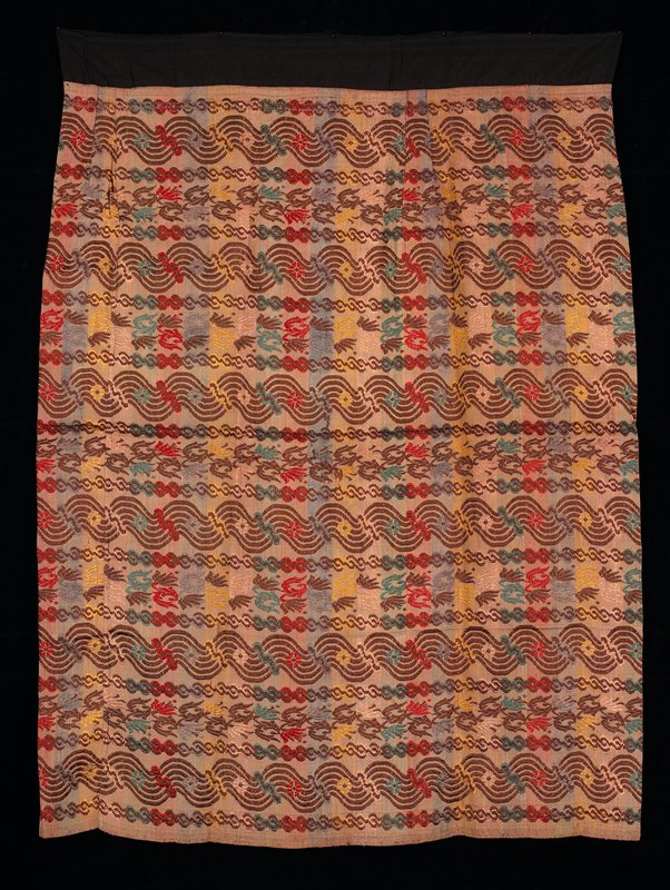 sarong with black band at top; background is vertical stripes in repeating pattern of pale blue, pale yellow, pale tan, pale brown, pale pink with horizontal repeating stitched pattern on top; stitched pattern in brown with red, yellow, green and blue accents