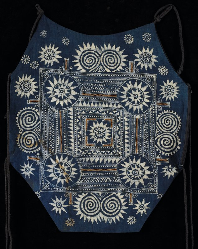blue and white batik pattern with flowers, swirls and geometric designs; embellished with gold cross-stitch embroidery; zipper on PL side allowing access to space between front and back panels; six ties