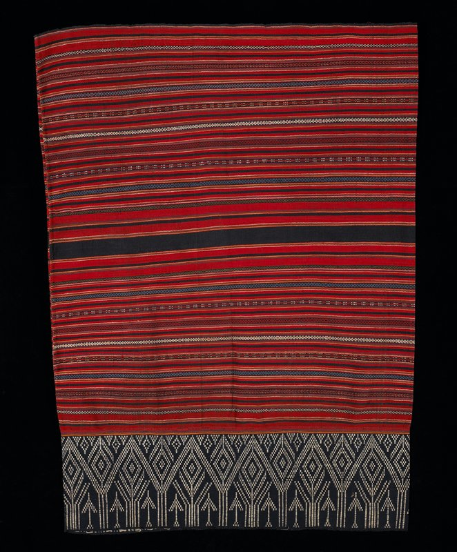 multicolored, striped skirt; geometric patterns, predominately red; wide navy and white band at one end