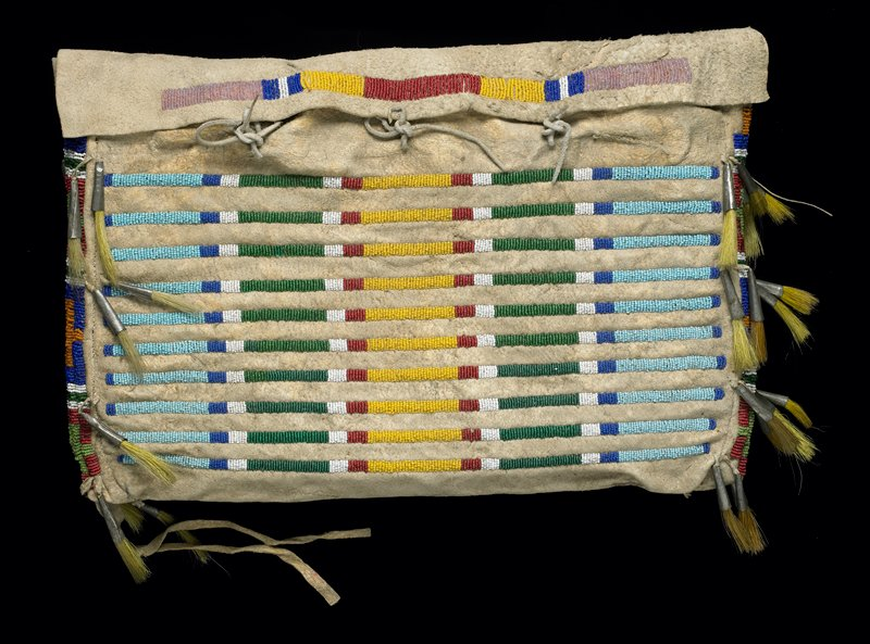 pouch with flap closure at top with three ties; ten identical separated stripes of multicolored beads in block design; one stripe on flap; cross motif beadwork, with bugle beads embellished with yellow horsehair, at sides; cloth back