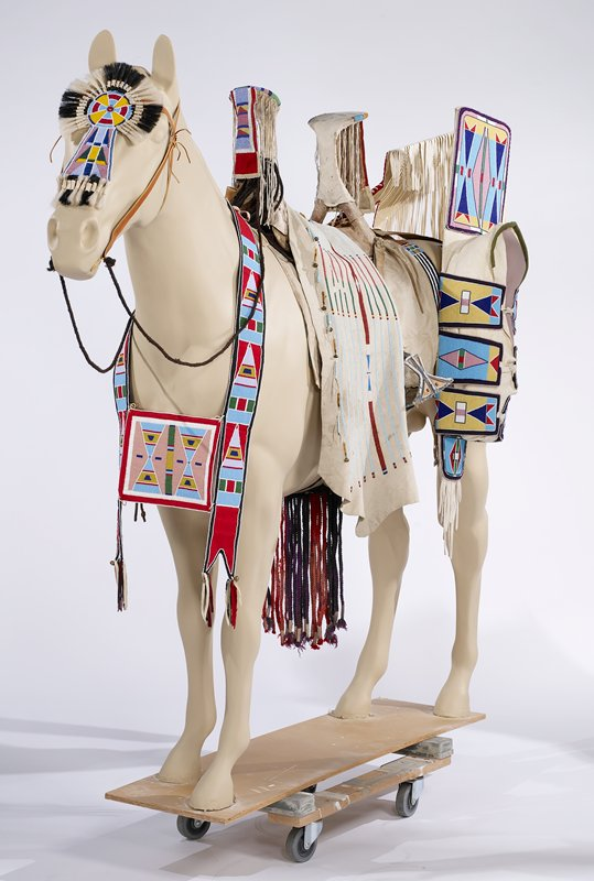 lower section is rawhide triangle, split at top to near bottom, with hole at bottom; decorated with triangles and blocks in red, blue, green and yellow; top section of tan cloth with hanging loop and padded top section; two straps of linear beadwork in red, blue and yellow
