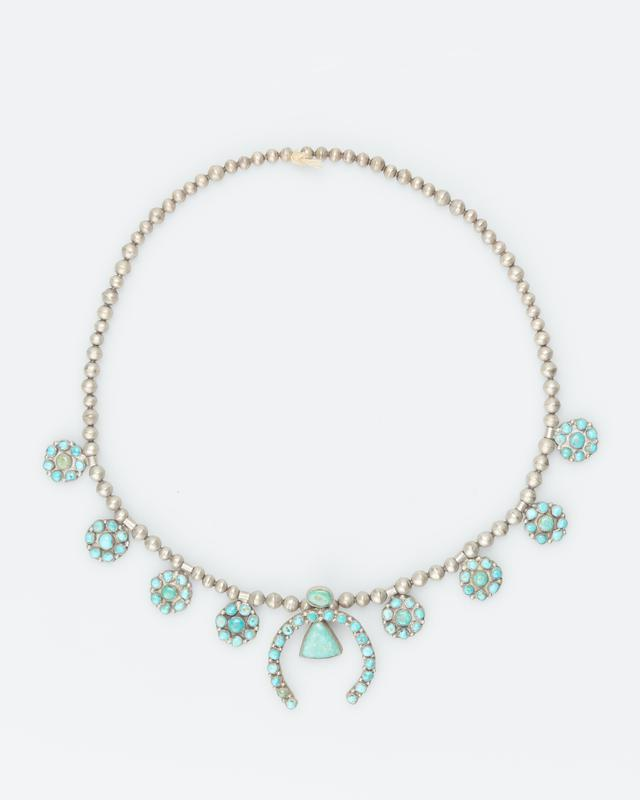 single strand of medium and small silver beads; 4 side clusters, 8 stones in each, on each side; naja of turquoise with silver drops between and triangular turquoise pendant; 84 stones in all; string with knot