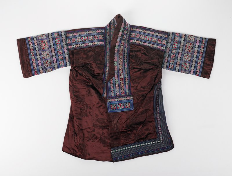 """brown silk damask with 6"""" longer front; open front with rows of blue, green, pink and white floral embroidery and applique on neck, front opening, yoke and sleeves; side opening on left has armhole with similar rows of embroidery with striped appliques which continue along hem in front and part way in back; blue lining"""