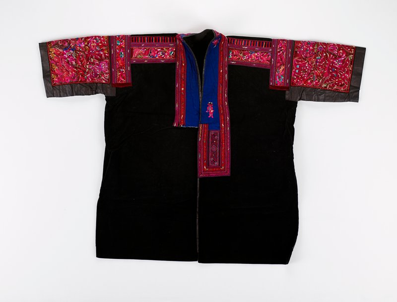 pounded indigo lining; black velvet jacket; front panels longer; side vents; pounded indigo cuffed sleeves; shoulder and yolk heavily embroidered with bird and dragons; multi-colored with red predominating; edged with gold and red narrow tape bordered by embroidered bands; neck edge has blue satin insert bordered by embroidered tape which encloses an intricate rectangular design applique on PL center; similar rectangular design at back of neck; three embroidered figures on blue satin insert; two woven front ties