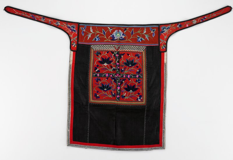 pounded indigo; top rust band and red ties are floral embroidered in blue and green; center square divided into four red squares with floral embroidery in blue, green, pink surrounded by applique strips; plain red, blue and white braid borders; black lining with lower edge hemmed separately