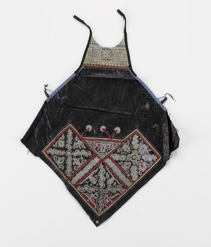 """pounded indigo diamond shape apron; added batik bib with 2 ties; lower half has sections of geometric embroidery in white, red, green divided by 1/4"""" applied red and green tape; three embroidered 3/4"""" medallions with multicolored 1 1/4"""" tassels at middle; 3/4"""" loops on sides tied with black string"""