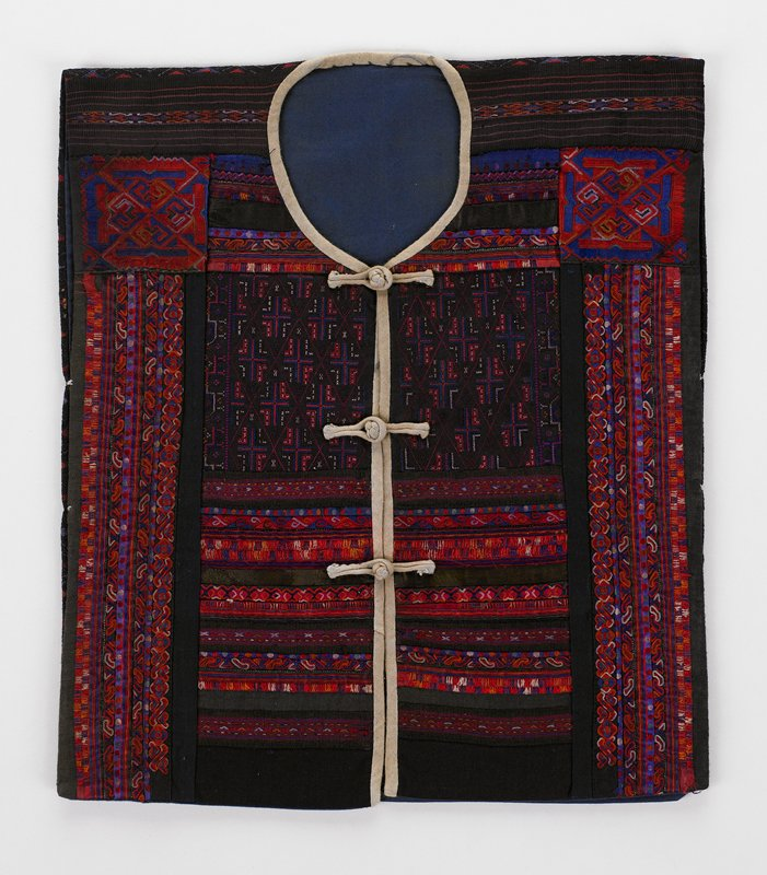 blue lining; back in diamond patterned silk-like weave; front heavily embroidered in horizontal and vertical patterns of scrolled geometric embroidery; shades of red, blue, orange on black background; Neck edge and front edge bound in white with three knot and loop closures