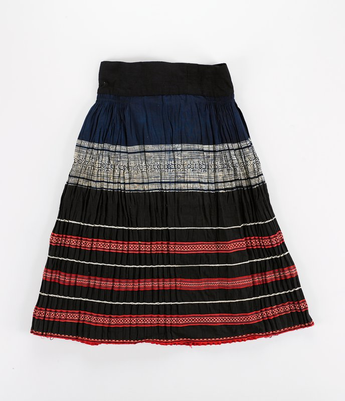 """top waist band (2-1/2"""") with loop and tie in black; top panel is blue/white batik; finely pleated on sides; lower portion pleated black twill with applied red ribbon with cross stitch embroidered bands; white narrow braid between"""
