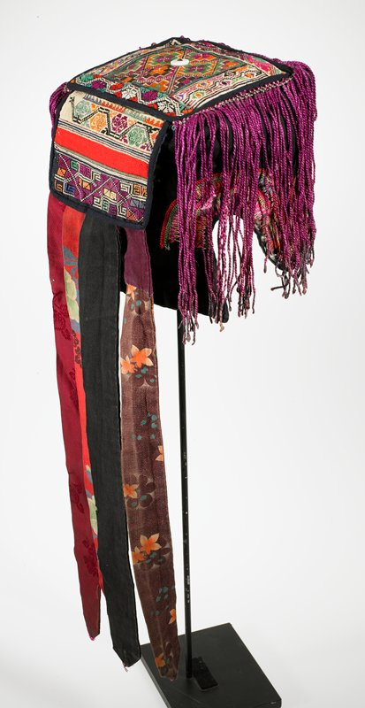 """black and multicolored; 2 squares of heavily embroidered bands cover top and back; four 16-1/2"""" streamers down back; edge of black cap embroidered; edged with small, pointed metal discs on three sides; shell on end of front tab; 7"""" wax-dipped purple fringe on three sides"""