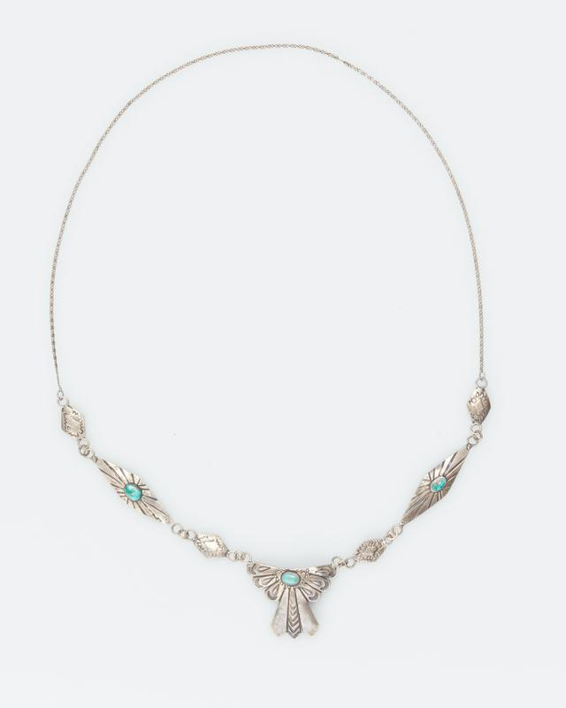 silver chain with hammered diamond shapes and a pendant ribbon design; two diamond pieces and the pendant have turquoise; pendant is bent on one side
