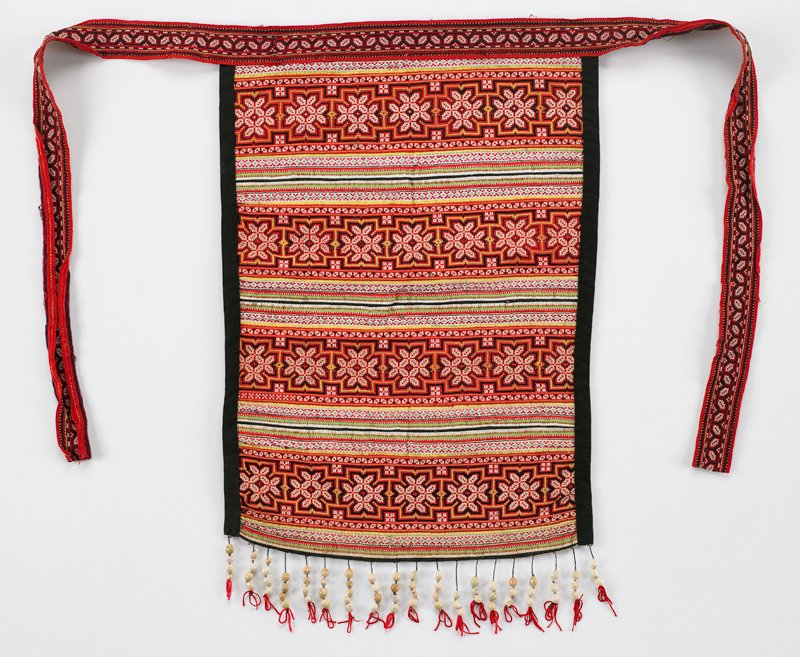 """rectangular apron with black side edges and seed fringe; geometric cross stitch bands in red and white separated by appliqued bands of orange, green, white, yellow and black; apron strings have geometric cross stitch in black and white on red; ties 20"""" long with white muslin lining"""
