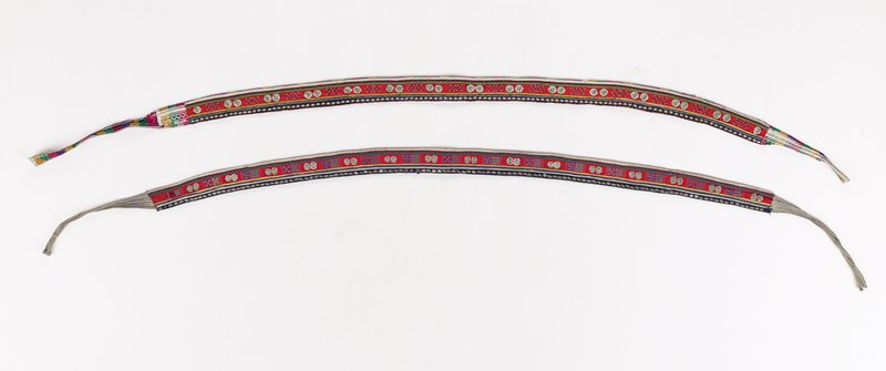center red strip with cross stitch alternating with raised metal flowers; bottom border has small metal ornaments on black applique; cotton ties