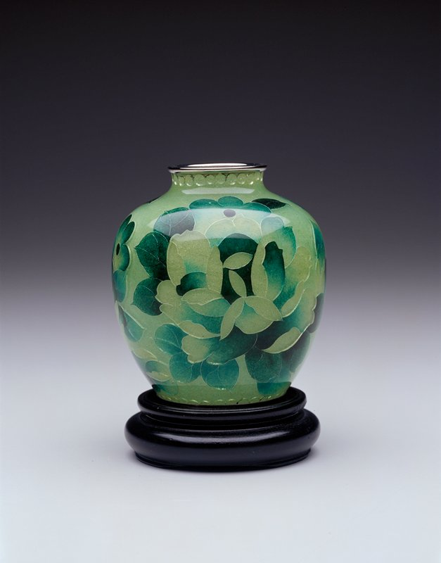 vase with floral design in shades of green; silver wire outlines; has wooden stand