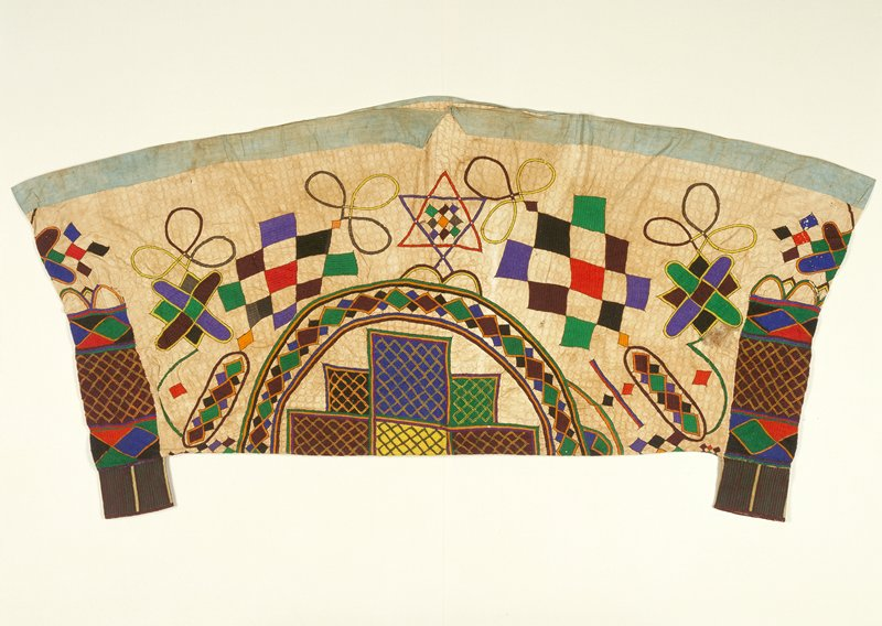 large piece of cloth with honey comb design, open on one long side with 2 short added open pieces at corners on opposite side; embroidered geometric designs overall; light blue hem