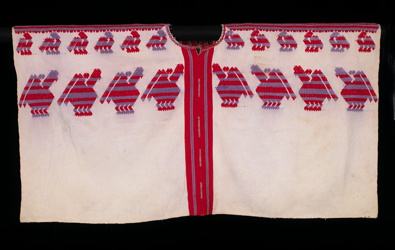 two white paneled cotton huipil; embroidered randa in red and purple; supplementary weft patterning; two rows of birds in red and purple; neckline embroidered