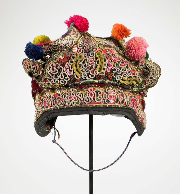 white, yellow, red, green; dark red velvet completely covered with appliqued designs using sequins; yellow metal; small white round braid in curly designs; six stiff peaks with pompoms; front has stiff, crown-like, free-standing piece; ear flaps; PL tie; quilted lining; chin strap