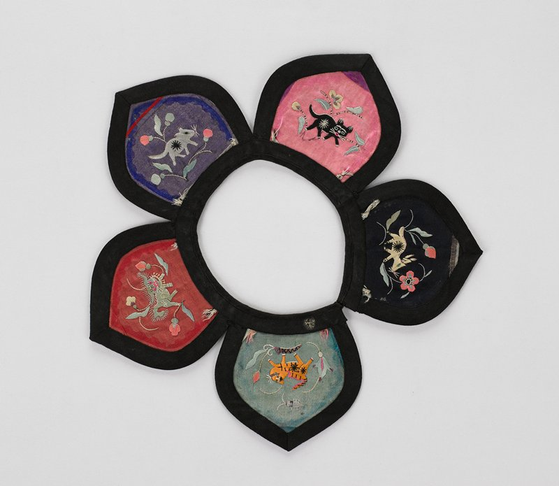 five petaled collar outlined in black; embroidered with animals and flowers on black, green, red, pink and purple silk pieces