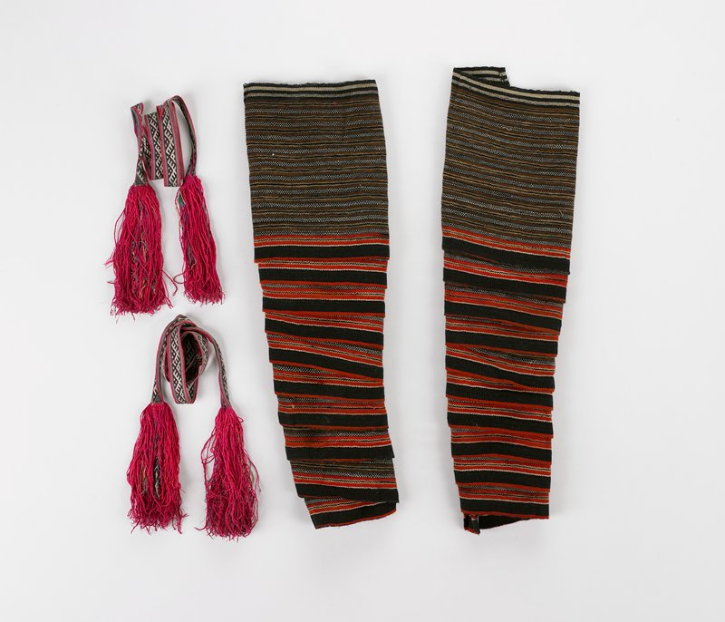 leg wraps: woven with striped horizontal bands in brown, black, red, white, beige in varying widths; ties: woven geometric pattern in red, green, black, white; extra red added to self-fringe
