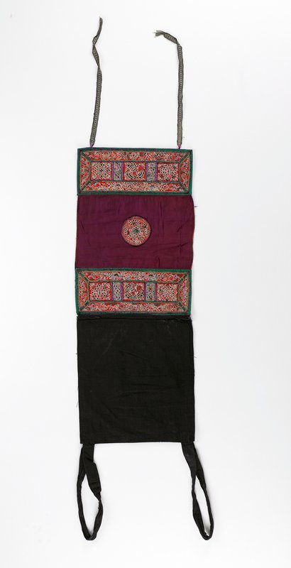"black lined top with straps; bottom section is silk maroon rectangle with center circle embroidered medallion; approx. 6"" embroidered borders, top and bottom; red background with five embroidered panels in frame; embroidery is metallic, white, purple, green and pink; end borders lined in black; two tapes hang from bottom"