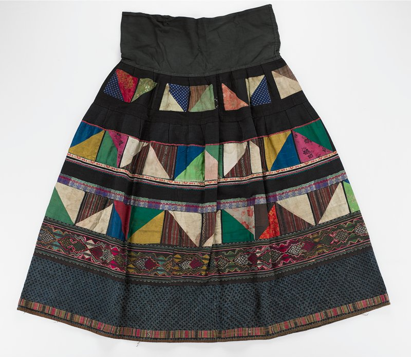 "black with separated rows of colorful, applied patchwork squares made of two triangles; bands of embroidery between the three rows; below this is a wide band of embroidery with some yellow metal couching; this is followed by 5-1/2"" band of indigo batik at lower edge; wide, 8-3/4"" black waistband; heavy"
