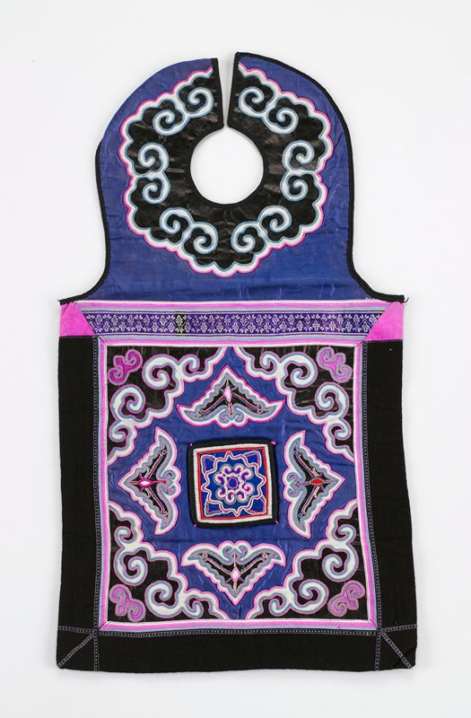 neck piece scroll appliques on pounded indigo on blue silk; bottom has a purple slik square bordered in black with eight irregularly-shaped appliques in pink and white; separate loose square appliques and embroidered patch attached to center of bottom section; black lining