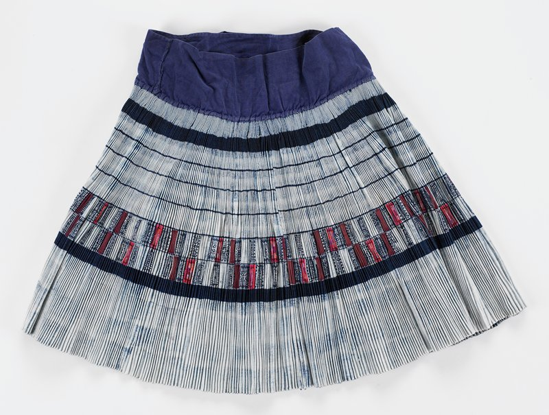 "accordion pleated wrap skirt with 3 1/4"" wide blue waistband and long ties; blue on white; tie-dyed; center horizontal 3"" band in geometric batik pattern; some appliqued embroidery in red and brown"