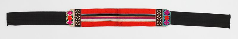 red and black; bands of red, white, black silk-like fabric sewn together with machine stitching; black cut-work; floral embroidery with yellow metal outlining, 3 red and purple satin-stitched petals one set on white and the other set on blue; wide black twill band at each end of sash; main section lined in pink checked fabric; machine stitched