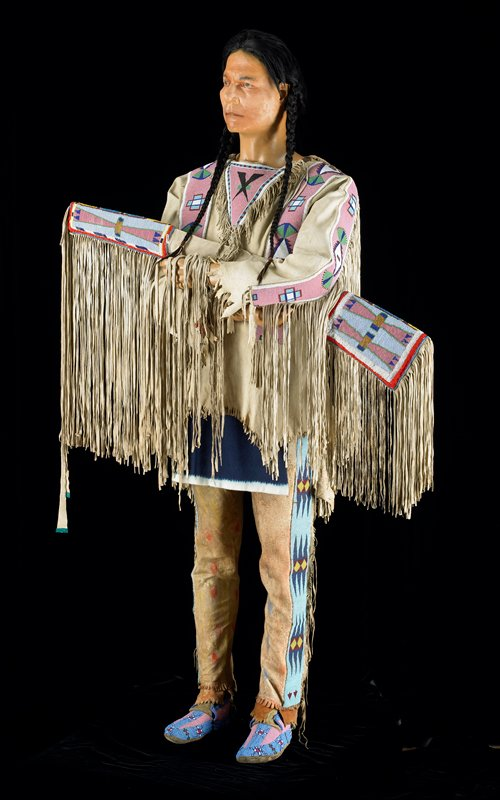 beaded sleeve with red cloth trim at muzzle end; beaded panel accented with eye-shaped and half-eye-shaped red fabric at butt; pink beads in small lines above long twisted fringe along barrel; thick fringe at butt end; multicolored geometric beading