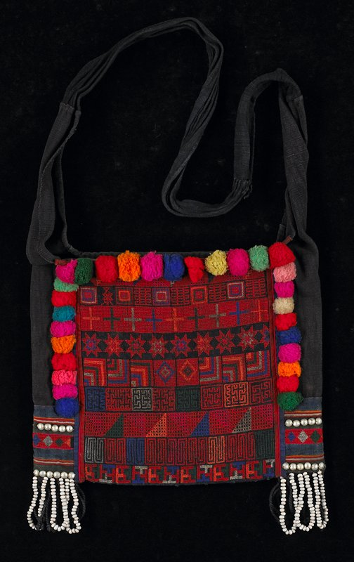 red, orange, blue cotton embroidery (cross stitch) on black cotton ground; wool pom-poms on three sides; metallic, half-round discs near bottom sides; twisted black and white seed fringe, bottom sides; black sides form shoulder strap; lined in tan; indigo reverse