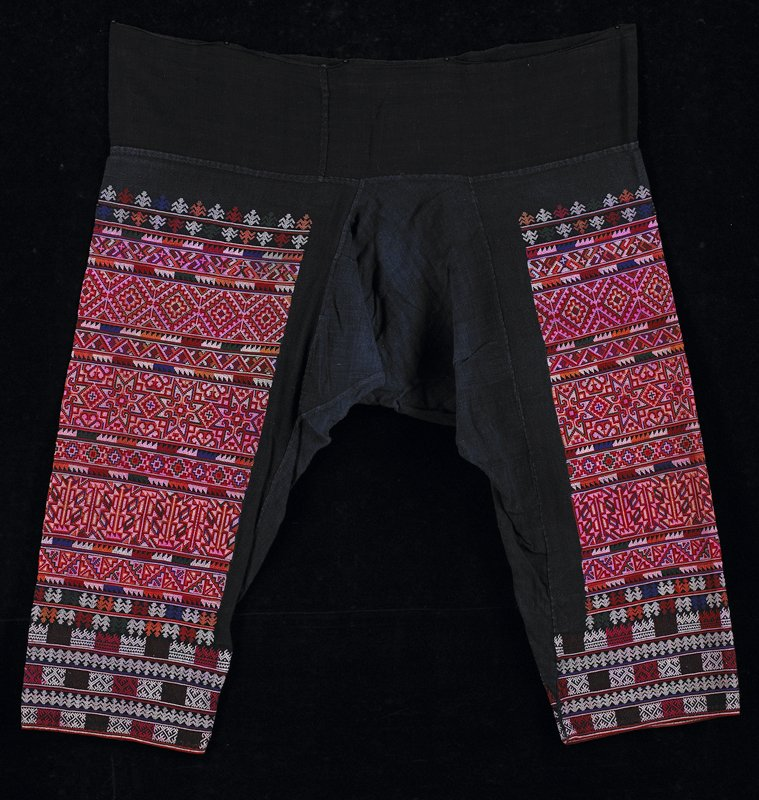 "blue/black cotton with geometric embroidery covering legs almost entirely; huge crotch ""gusset""; wide black waist band; embroidery is red, pink, purple, green and white"