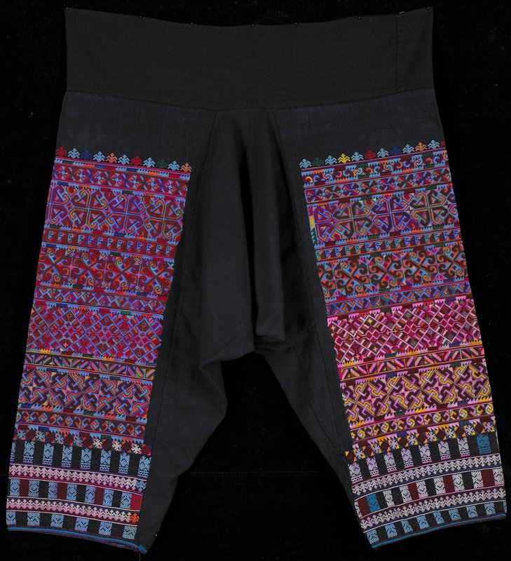 most of legs covered with geometric bands of embroidery in predominately red and blue; pattern is same on each leg but colors vary; wide black band; voluminous crotch