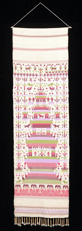 off-white background with supplimentary weft green, dark red, pink, mauve patterning at center--architecture with figures and animals around wood rod at top and fringe of bamboo pieces at bottom